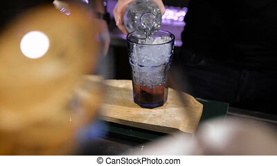 Bartender is making cocktail. pouring soda into a glass with ice