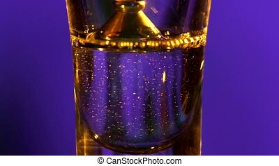 Bartender is pouring a drink into a glass with white liquid,...
