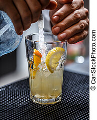 Bartender is pouring soda water, he is preparing a cocktail