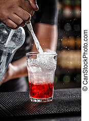 Bartender is pouring soda water, he is preparing a raspberry...