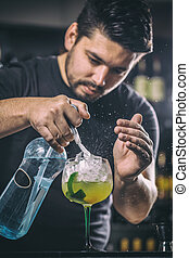 Bartender is pouring soda water, he is preparing a mango...