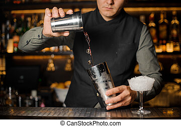 Bartender mixing drinks for making a cocktail