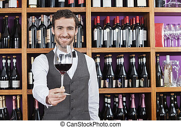 Bartender Offering Red Wine Glass Against Shelves