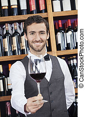 Bartender Offering Red Wine Glass In Winery