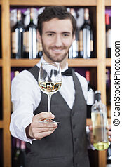 Bartender Offering White Wine Glass Against Shelves