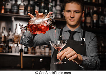 Bartender pouring an alcoholic drink into the cocktail glass