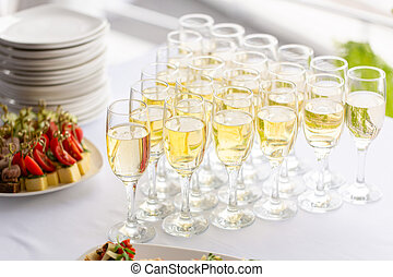 Bartender pouring champagne or wine into wine glasses on the table in restaurant. solemn wedding ceremony or happy new year banquet