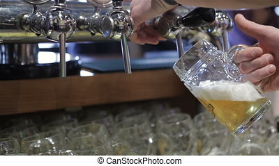 Bartender pouring draft beer in the bar. Detail of a hand...