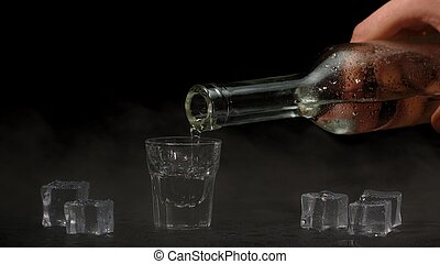 Bartender pouring up shot of vodka with ice cubes from bottle into shot glass on black background