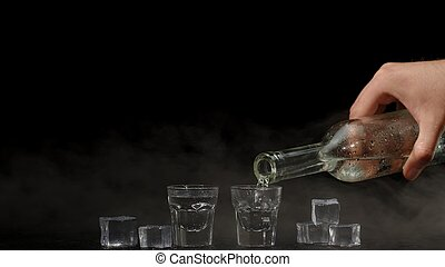 Bartender pouring up two shots of vodka with ice cubes from bottle into glasses on black background