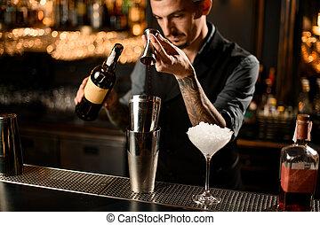 Bartender pouring whiskey from jigger to shaker