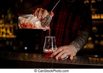 Bartender pourring a Sazerac cocktail from the glass measuring cup