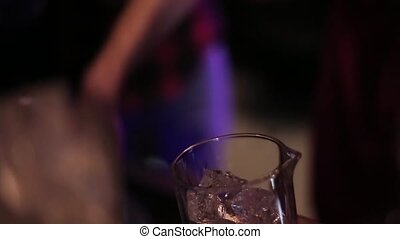 Bartender pours a glass of ice closeup