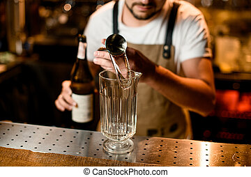 Bartender pours cocktail with stainless steel jigger