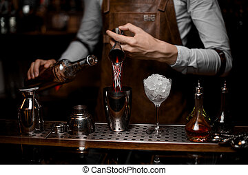 Bartender pours drink from jigger to shaker