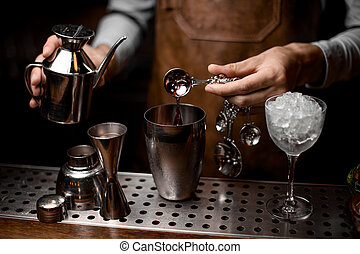 Bartender pours drink with kettle, spoon and shaker