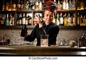 Bartender pours liquor from bottle with jigger