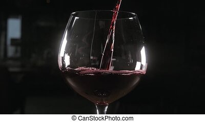 Bartender pours red wine in glass from big transparent...