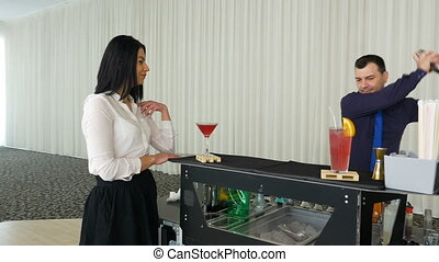 Bartender preparing cocktail for lady waiting by the mobile...