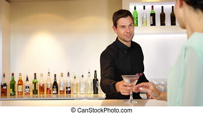 Bartender serving a cocktail and chatting to customer at the...