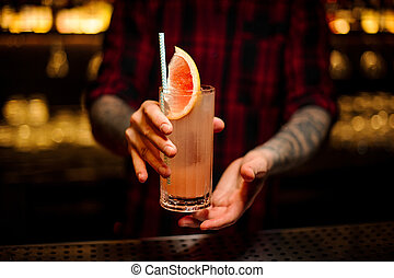 Bartender serving a glass of a delicious cocktail with grapefruit on the bar counter