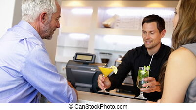 Bartender serving cocktails and chatting to customers at the...