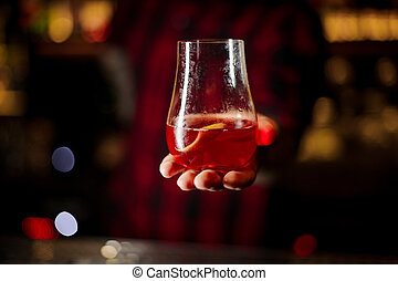 Bartender serving glass of a Sazerac cocktail