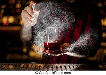 Bartender spraying on the Sazerac cocktail in the bar