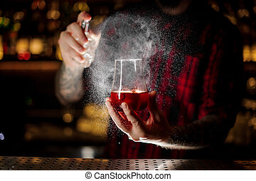 Bartender spraying on the Sazerac cocktail in the glass