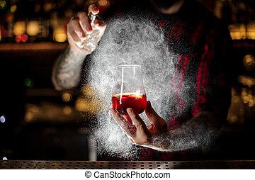 Bartender spraying on the Sazerac cocktail with orange zest