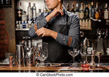 Bartender standing behind the bar counter with a bar equipment