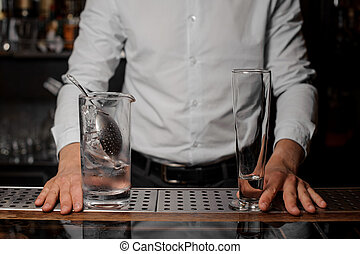 Bartender standing behind the bar counter with glasses on it
