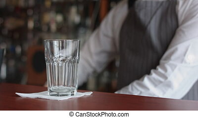 Bartender turns the ice with spoon - Bartender turns the ice...