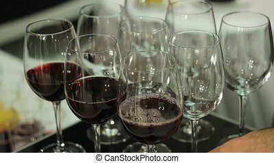 bartenders hands pouring up glasses with red wine.