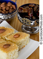 Basbousa on a Plate with a Bowl of Dates and Almonds