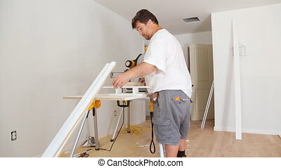 Base trim the miter saw Carpenter cutting wood - Carpenter...