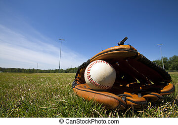Baseball and Glove - A white baseball in a brown leather...
