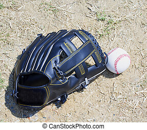Baseball and glove over dirt