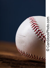 Baseball ball on wooden table and blue backgdound