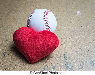 Baseball ball with a red heart on a wooden surface
