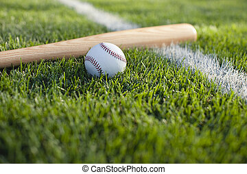 Baseball bat and ball on grass near field stripe - A...