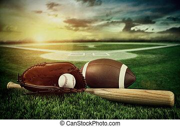 Baseball, bat, and mitt in field at sunset