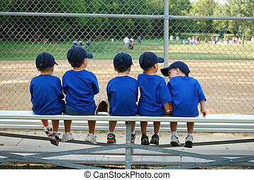 little boys sit on a bench waiting for their baseball game to start