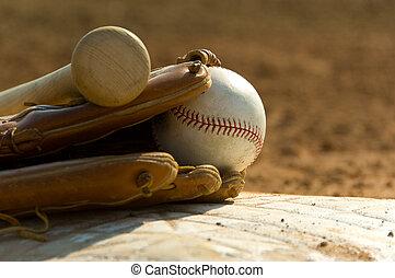 Baseball equipment on base - Baseball bat, glove and ball on...