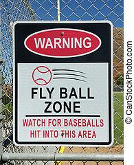 Baseball fly ball zone warning sign on fence