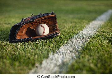 Baseball mitt and ball in grass by field stripe - A...