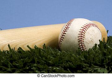Baseball on Grass with bat against blue sky