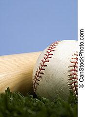 Baseball on Grass with bat agaist blue sky