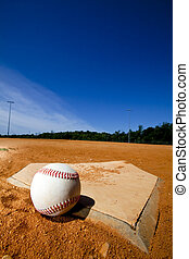 Baseball on Homeplate - A baseball on a dirty homeplate with...