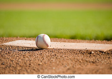 Baseball on Mound - A white leather baseball lying on top of...